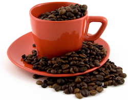 A picture of a coffee cup filled with coffee beans - the ultimate magic beans for improving tech copywriting and creativity